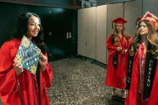 Females graduate holding her graduation cap with BSN on the cap, and two female graduates with BSN on their robes.