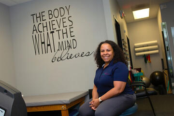 """A woman sits in front of a sign reading """"The Body Achieves What the Mind Believes"""""""