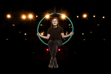 woman sitting in hoop above stage