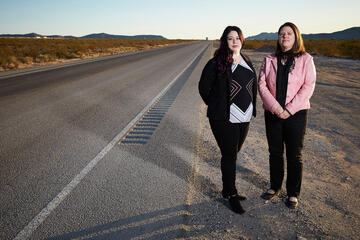 two women standing next to empty road