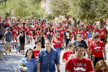 Students in red shirts walking outside on campus