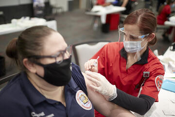 nurse administers shot to woman