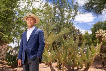 Portrait of Sam Fugazzotto standing in front of cacti