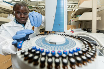 man in lab coat using equipment in a university laboratory