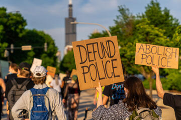 """Protest signs read """"Defund Police"""" and """"Abolish Police"""""""