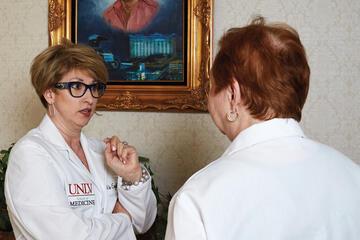 Two women in white coats talk.