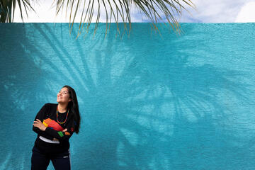 A woman stands next to a turquoise blue wall in the shadow of palm trees