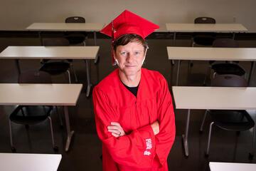 A man in graduation regalia stands in a classroom