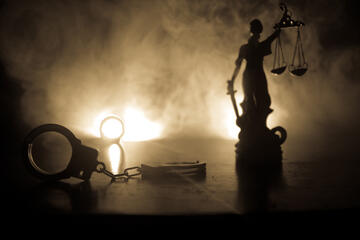 Handcuffs are laid at the feet of a statue holding the scales of justice