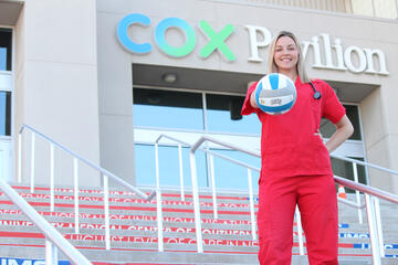 A woman in nursing scrubs holds a volleyball