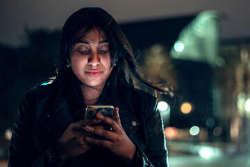 A woman looks at her phone in front of Lied Library