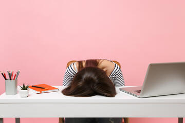 A woman's head is face-down on a desk in frustration