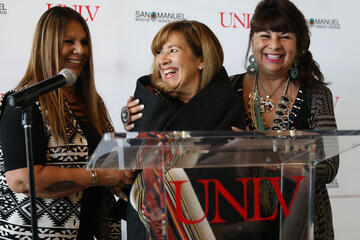 Representatives from the San Manuel Band of Mission Indians wrap UNLV Marta Meana in a blanket as part of the tribe's gift announcement to the university.