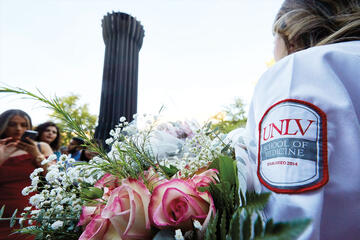 A student wears a white coat with a patch that reads 'UNLV School of Medicine'