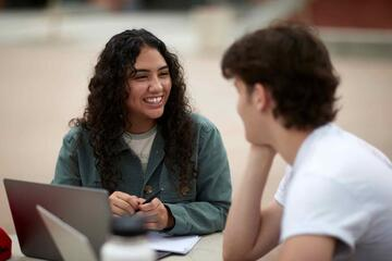 Blanca Pena (left) talks at a table with another student.