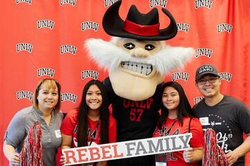 "A group of four people standing with mascot Hey Reb! holding a ""Rebel Family"" sign."