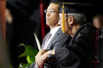 A man in a gown and mortarboard sits flanked by his son