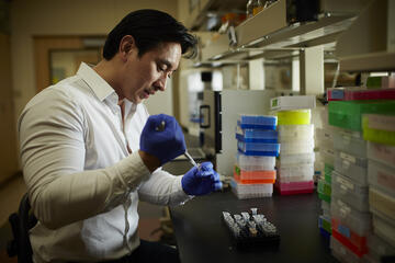 UNLV researcher Edwin Oh holds a pipette in his lab on campus.