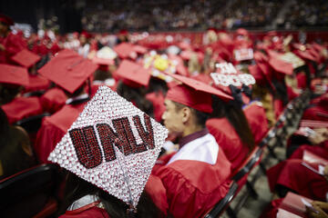 Decorated UNLV mortarboard with students in background