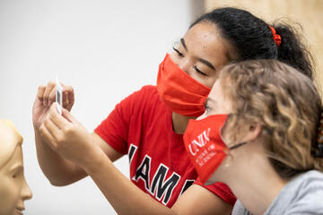 UNLV nursing student in red shirt reviewing slide sample with peer