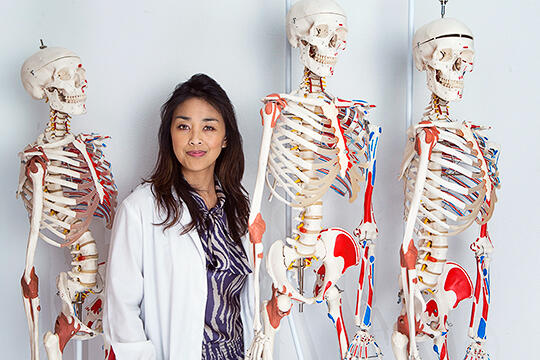 Jennifer Kawi poses next to three skeletons