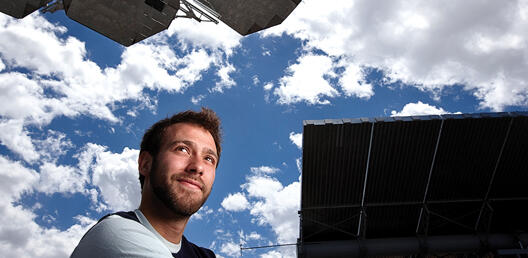 man stands by solar array