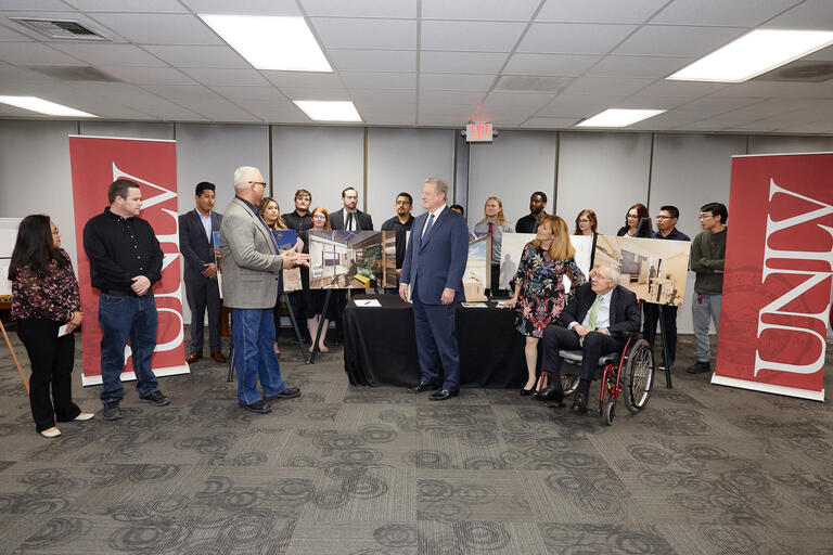 Al Gore, Senator Harry Reid, and President Marta Meana stand with a group of 15 students and their advisor in front of posters with drawings for a solar home.