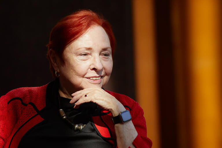 A woman with red hair rests her hadn on her chin