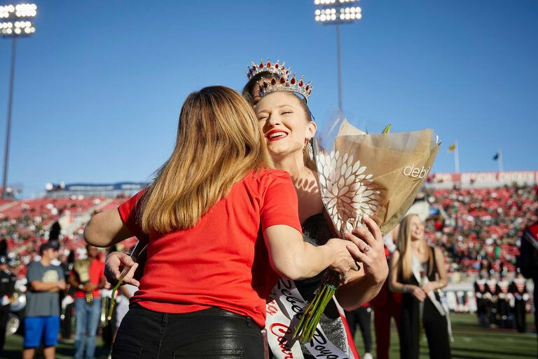 A student hugs the UNLV president while holding a bouquet and wearing a crown at a football game.