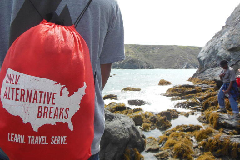 student with red Alternative Breaks backpack facing a rocky ocean coast