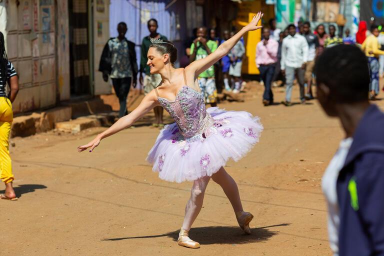 A woman in a ballet tutu dances in an African city