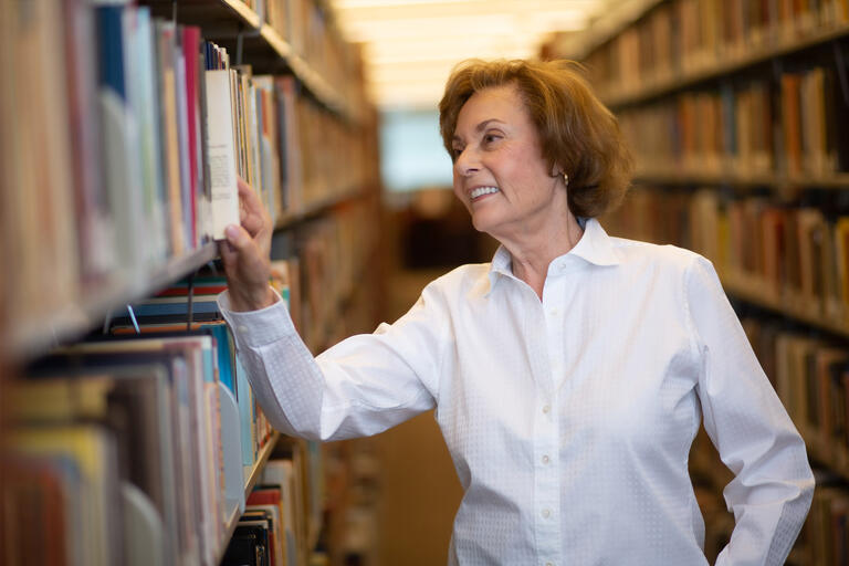 A woman looks at a book on a library shelf