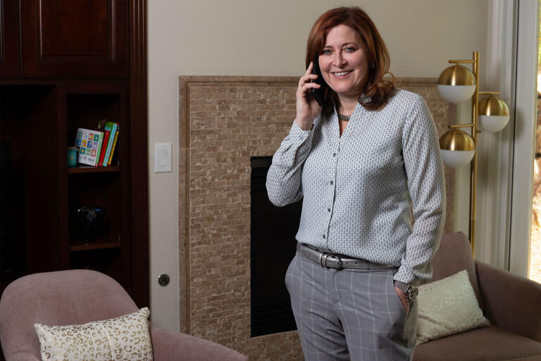A woman stands in a living room holding a telephone to her ear