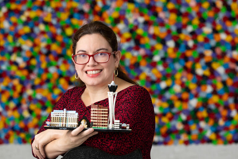 A woman holds up a Lego version of the Las Vegas Strip