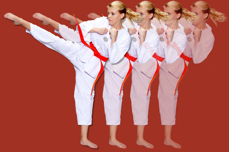 A woman in a karate gi kicks.