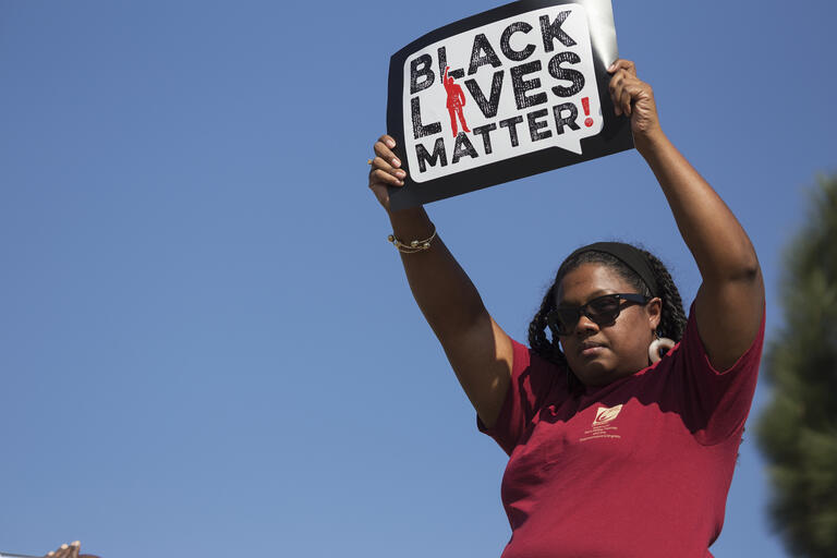 "protester holding sign that reads, ""Black Lives Matter"""