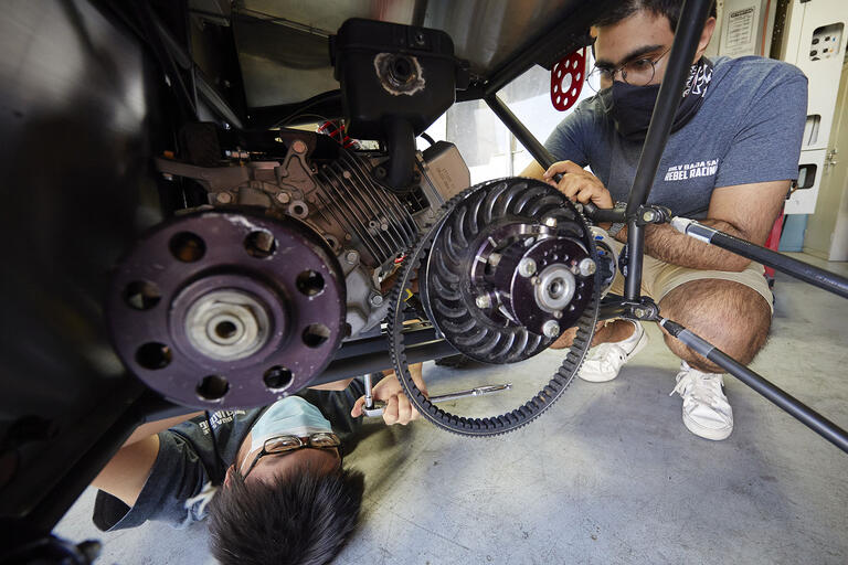 two people working on an engine