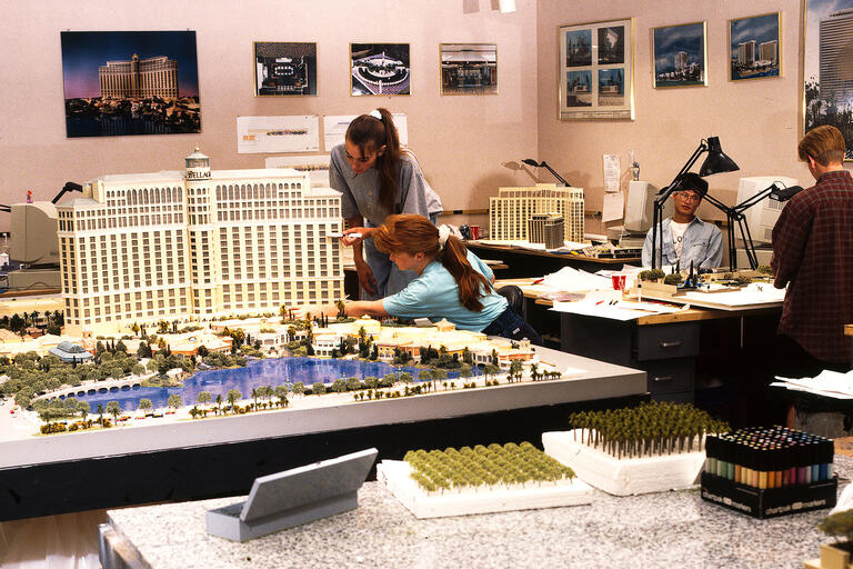 Two workers lean in to work on a model of the Bellagio.