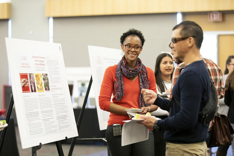 Woman talking to man in front of academic research poster