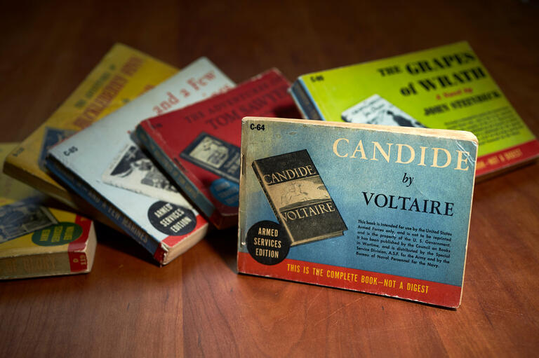 A pile of books is topped by a special edition of Candide by Voltaire.