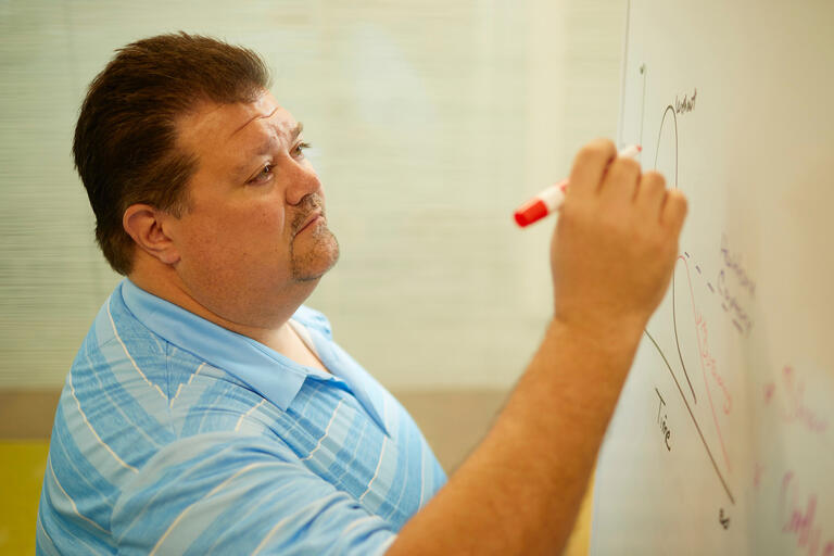 A man in a blue striped shirt writes on a whiteboard.