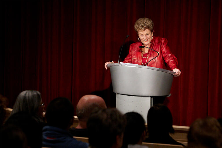 A woman in a red jacket stands at a podium and smiles