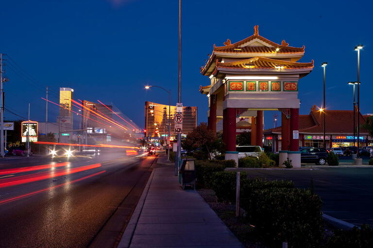 Commercial building with Asian architecture at night with car lights streaming