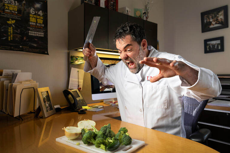 A chef raises a cleaver to chop and onion and broccoli.