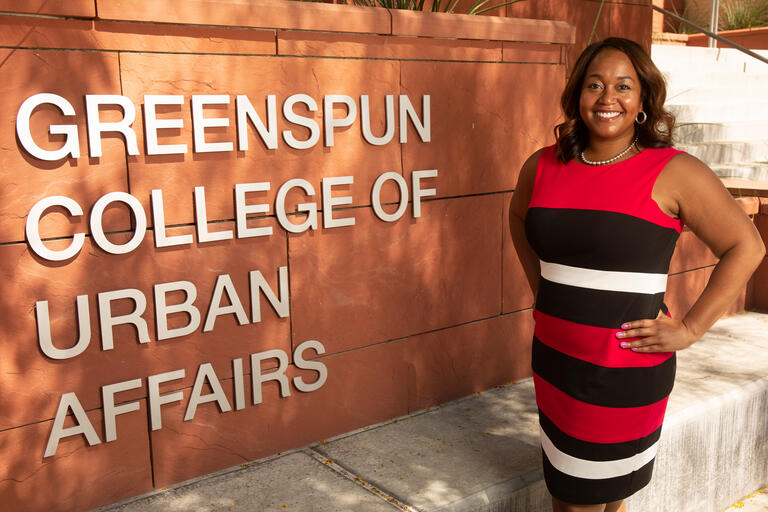 A woman in a red and black dress stands next to the College of Urban Affairs sign