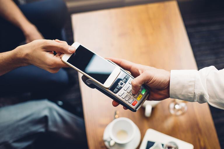 A smartphone is used to enact a contactless payment at a restaurant