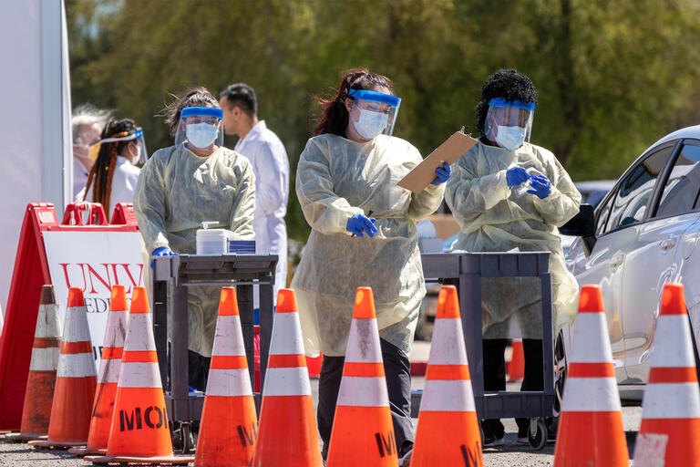 A group of health officials in protective equipment wait for al ine of cars passing orange cones