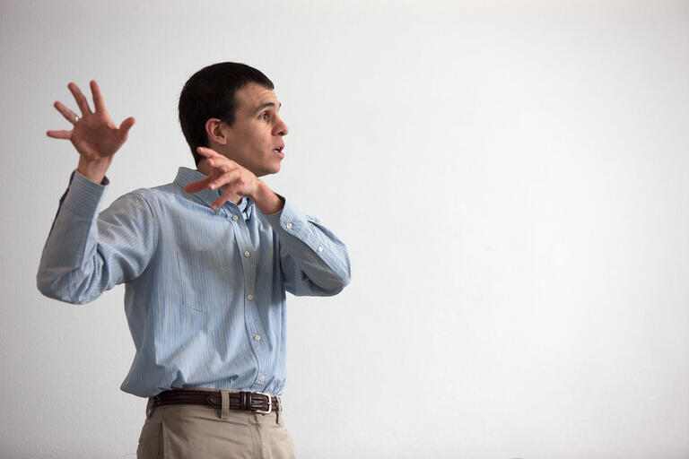 man gestures while teaching