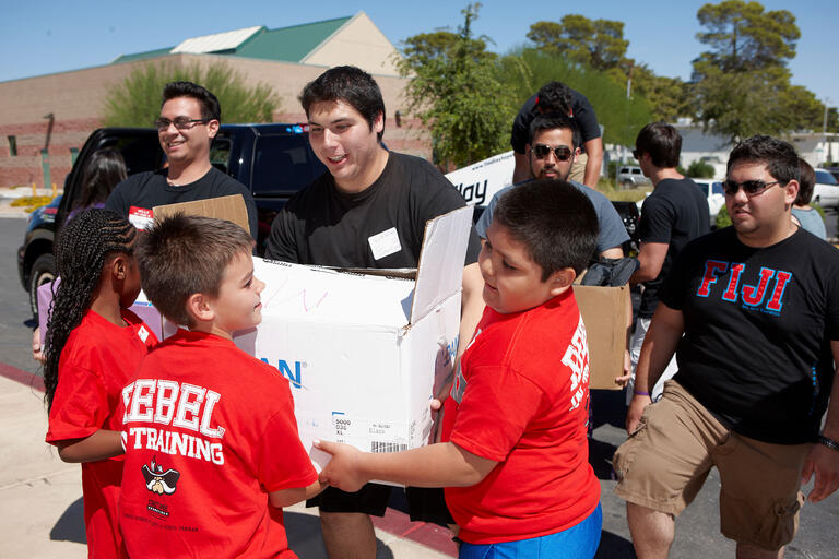 Younger kids help out rebel students move boxes.