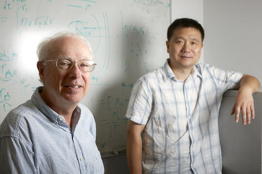 Donor Russell Frank and astrophysics professor Bing Zhang standing in front of a whiteboard.